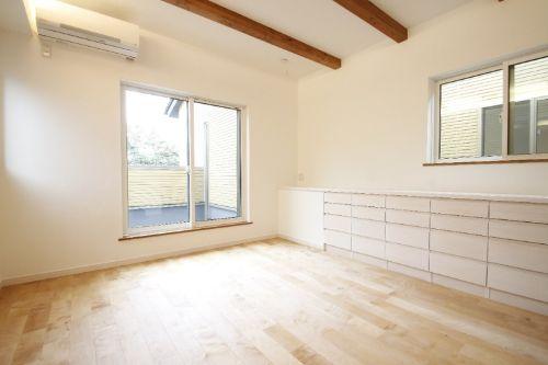 白い壁に淡い色のフローリングを合わせた寝室